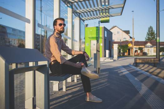 Man Wearing Sunglasses Sitting at Bus Stop during Daytime #37752