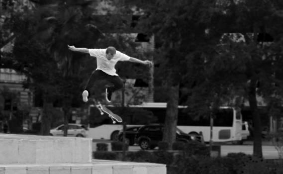 Man in White Shirt and Black Pants Playing Skateboard Near Green Tree during Daytime #38210