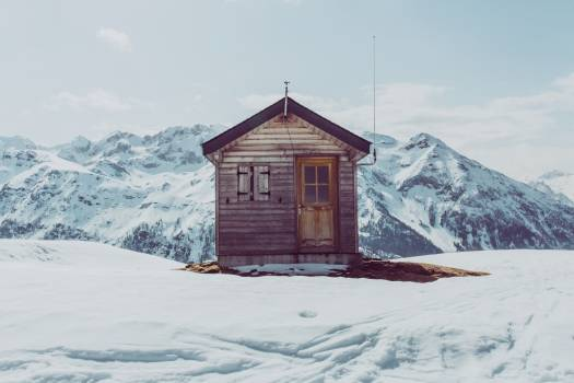Brown Wooden Bunk House Surrounded by Snow Covered Ground and Mountains during Daytime #38257