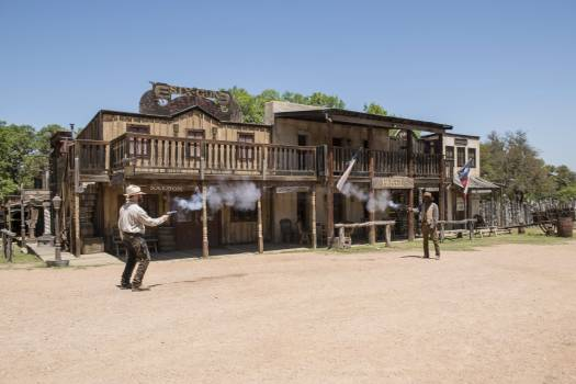 """Two """"gunslingers"""" (historical intrepreters Wes Hughes, left, and Thornton Young) fire away in a showdown on the street at the Enchanted Springs Ranch and Old West theme park, special-events venue, and frequent movie and television-commercial set in Boerne Free Photo"""