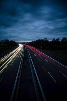 Road with long exposure lights on a cloudy night Free Photo