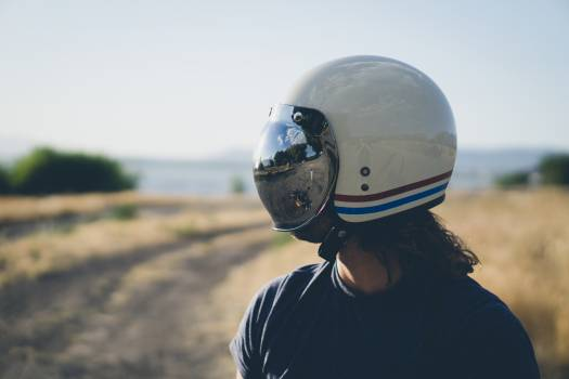 Person in Black Crew Neck Shirt Wearing White Red and Blue Helmet Standing on Field Free Photo