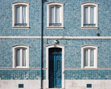 Blue Wooden Door With White Door Frame on Blue Concrete Building Free Photo