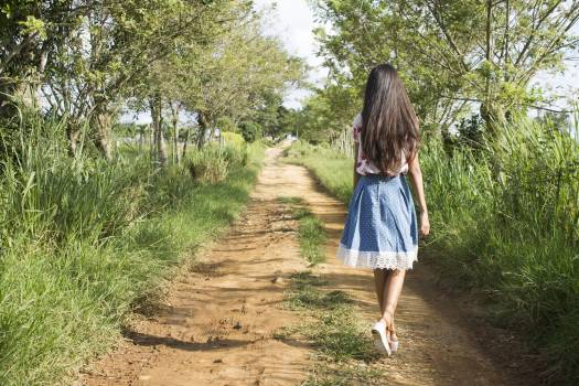 Woman Wearing Blue and White Skirt Walking Near Green Grass during Daytime Free Photo