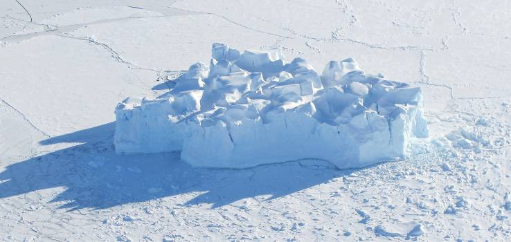 An iceberg embedded in sea ice as seen from the IceBridge DC-8 over the Bellingshausen Sea on Oct. 19, 2012. Original from NASA.  #385449