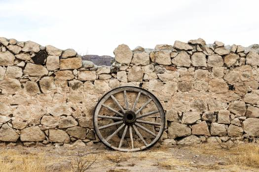Wagon wheel against a stone fence at Hueco Tanks State Park, northwest of El Paso, USA. Original image from Carol M. Highsmith's America, Library of Congress collection.  #385796
