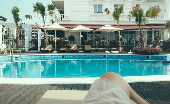Person Relaxing Near a Swimming Pool Free Photo