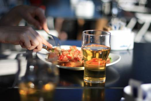 Pilsner Glass With Beer Beside White Plate Free Photo