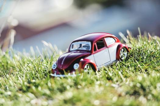 Red and White Beetle Car Toy on Grass Field in Bokeh Photography Free Photo