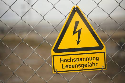 High voltage warning sign hanging on a fence Free Photo