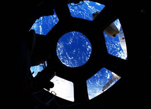 A blue and white part of Earth is visible through the windows in the Cupola of the International Space Station, 22 August 2011. Original from NASA.  #393052