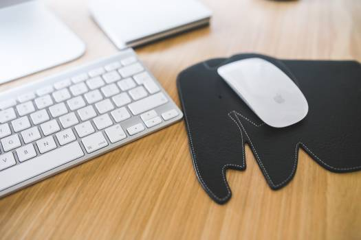 White Apple mouse and keyboard on the black Elephant Pad #39836