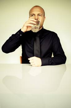 Man in Black Dress Shirt Sitting in Front of White Table Drinking Water #39843