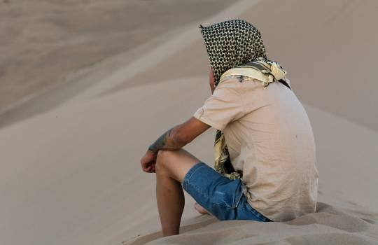 A lonely man sitting on a sand dune - free stock photo #398769
