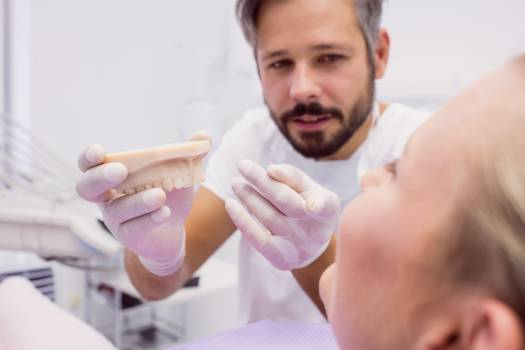 Dentist showing denture model to the patient #409390