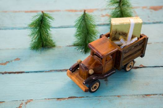 Toy tempo carrying christmas present on wooden plank #409402