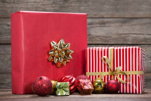 Wrapped gift boxes and baubles on wooden table #409423