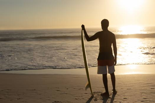 Man standing with surfboard on the beach #409428