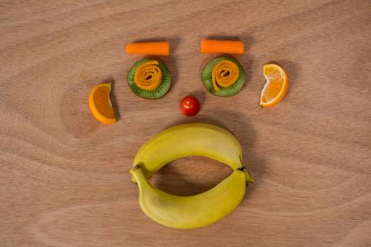 Face made up of fruits on a table Free Photo