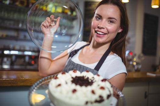 Portrait of waitress holding a plate of cake Free Photo
