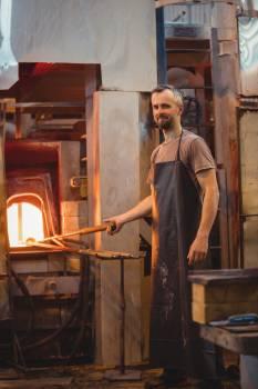 Glassblower heating a glass in glassblowers oven #409535