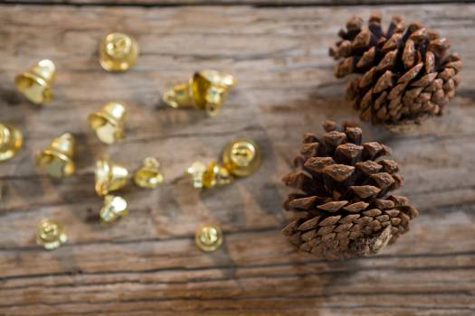 Christmas bells and pine cone on wooden plank #409555