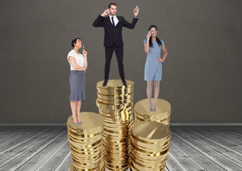 Businesspeople standing on stacked coins against grey background #409669