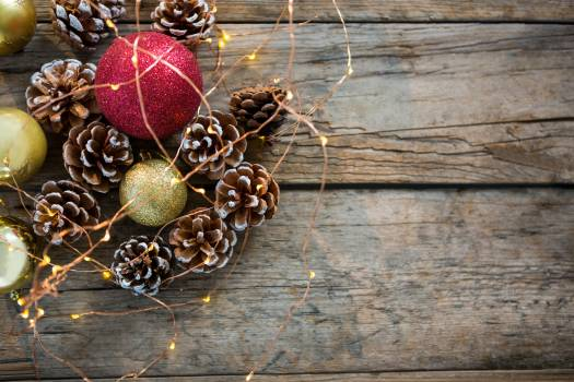 Close-up of rice lights, bauble ball and pine cone on wooden plank #409710