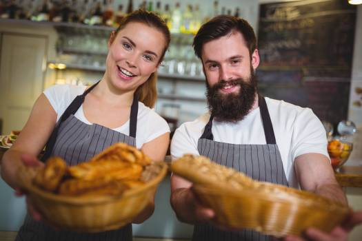 Portrait of waiter and waitress holding a basket of bread #409742