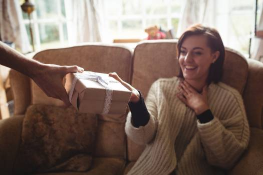 Man surprising woman with a gift in living room Free Photo