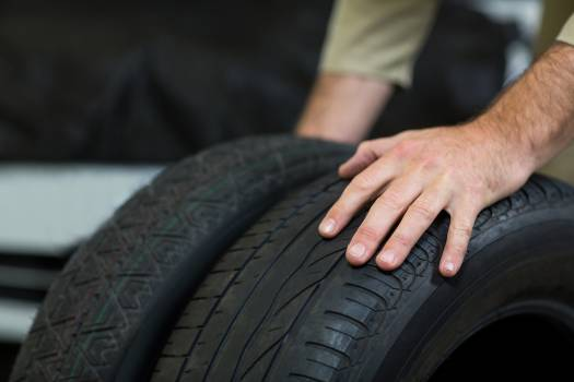 Hands of mechanic touching tyres Free Photo