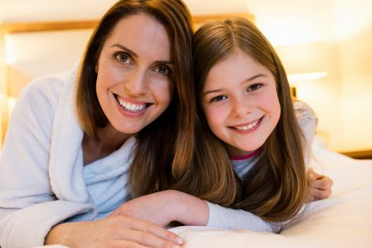 Portrait of mother and daughter lying on bed Free Photo