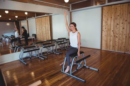 Trainer helping a woman while practicing pilates Free Photo