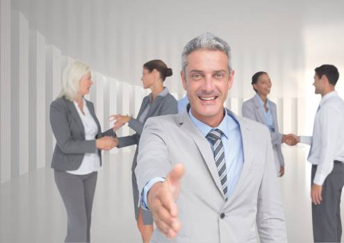 Smiling businessman offering his hand for a handshake against colleagues in background #409775