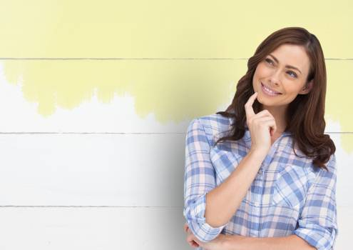 Woman thinking against painted wall #409799
