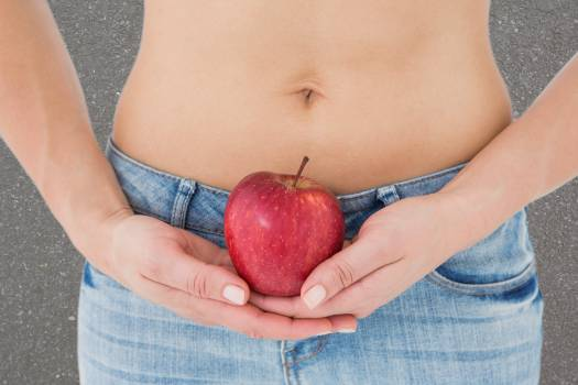 Midsection of woman holding apple representing weight loss #409801