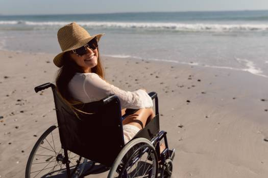 Disabled woman in hat and sunglasses sitting on wheelchair at beach in the sunshine #409809