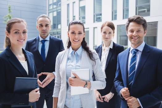 Confident businesspeople standing outside office building Free Photo