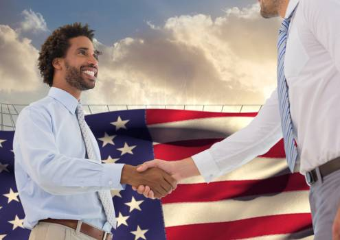 Businessmen shaking hands against american flag in the background #409852