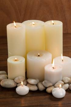Close- up of white candles and pebbles stone on wood #409922
