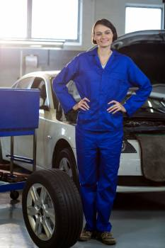 Portrait of female mechanic standing with a tyre #409935