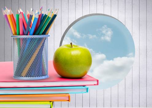 Apple and colour pencils on books against sky background #409943