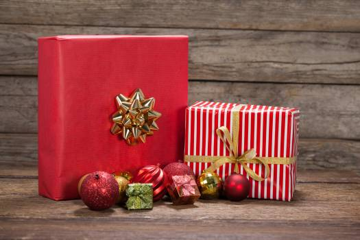 Red color Christmas decoration and gifts kept on wooden table #409955