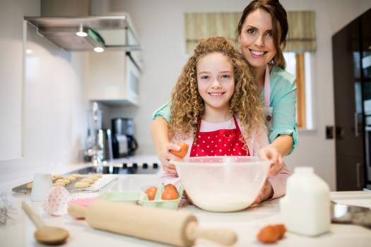 Mother assisting daughter in breaking eggs in kitchen #409961