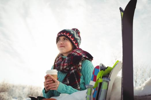 Skier woman with coffee cup looking up and smiling #409991