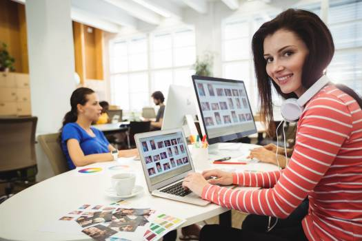 Graphic designer looking at camera while colleague working in background Free Photo