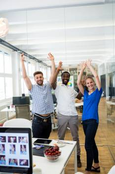 Group of graphic designers raising arms Free Photo