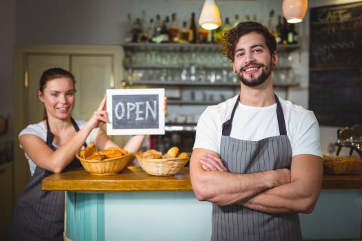 Waiter standing with arms crossed at counter in café Free Photo