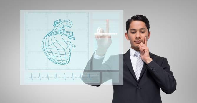 Thoughtful businessman touching human heart graphic on a digital wall Free Photo