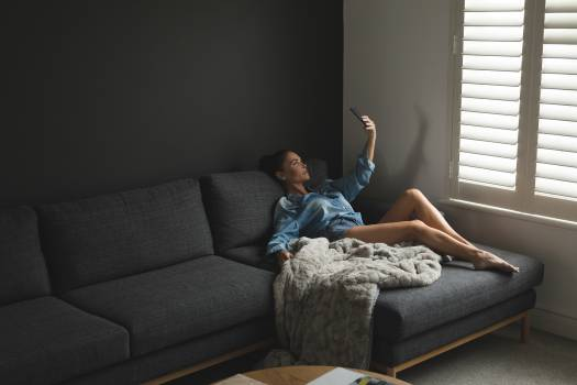 Woman taking selfie while relaxing on sofa in a comfortable home #410105